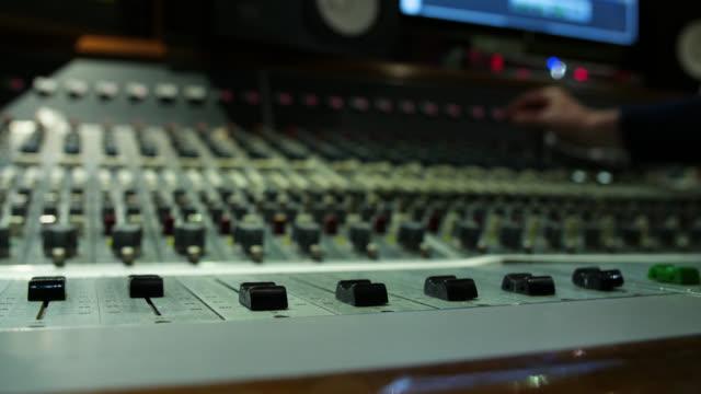 vidéos et rushes de low angle panning shot across a sound mixing desk in use - matériel d'enregistrement