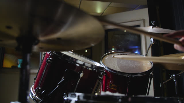 low angle panning shot of a drum kit being played in slow motion - drummer stock videos & royalty-free footage