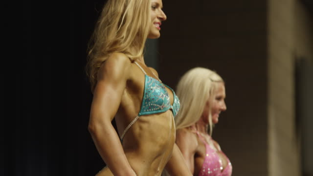 low angle panning shot of bodybuilders posing on stage at competition / draper, utah, united states - body building stock videos & royalty-free footage