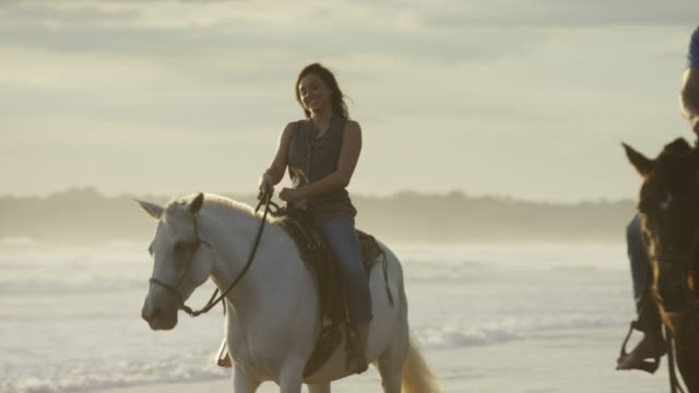 stockvideo's en b-roll-footage met low angle panning shot of couple riding horseback on beach / esterillos, puntarenas, costa rica - recreatief paardrijden