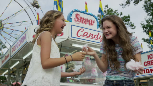 vídeos y material grabado en eventos de stock de low angle panning shot of girls eating cotton candy at funfair / pleasant grove, utah, united states - noria