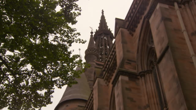 low angle panning shot of green tree by university building in city against sky - glasgow, scotland - church stock videos & royalty-free footage