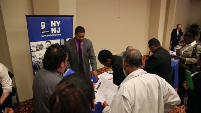 Low angle panning shot of people applying for various jobs Job seekers meet potential employers at a job fair held in a conference room of the...