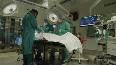 low angle panning shot of surgeons operating on patient / salt lake city, utah, united states - medical occupation stock videos & royalty-free footage
