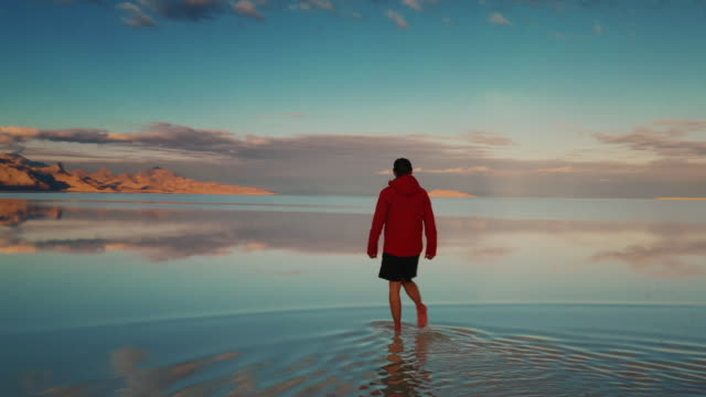 stockvideo's en b-roll-footage met low angle panning shot showing a young male walking on the flooded bonneville salt flats, utah, united states of america - bonneville zoutvlakte
