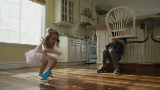 """Low angle panning slow motion shot of girl dropping cup on kitchen floor / Cedar Hills, Utah, United States"""