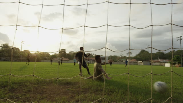 Low angle panning wide shot of soccer player scoring goal and cheering / Esterillos, Puntarenas, Costa Rica