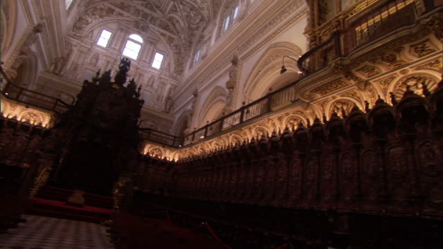 low angle pan-right - a throne ensconced in a dimly illuminated room is adjacent to a bright white chapel below a coffered ceiling. / cordoba, spain - throne stock videos & royalty-free footage