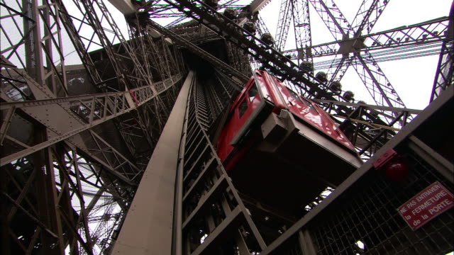 low angle pan-right - an elevator takes visitors to the observation deck of the eiffel tower. / paris, france - eiffel tower paris stock videos & royalty-free footage