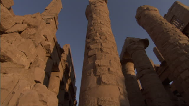 Low Angle, pan-right - Spires of old adobe buildings stand against a clear blue sky / Egypt