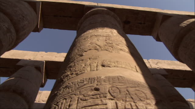 Low Angle, pan-right tracking-right - Carvings of hieroglyphs cover the columns of ancient adobe buildings / Egypt