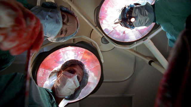 Low angle patient point of view surgeon and nurses looking down while performing surgery with bloody gloves