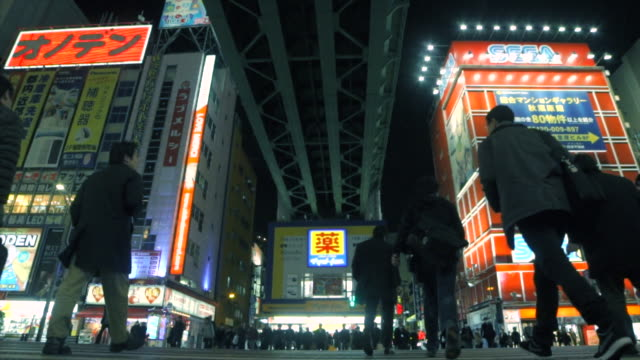 Low angle - pedestrians crossing crosswalk at night - Japan