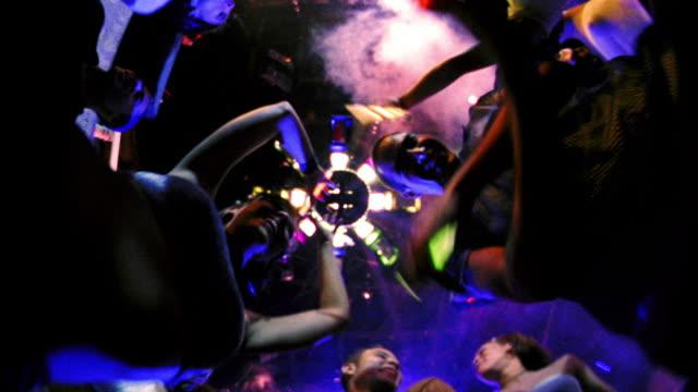 vídeos de stock, filmes e b-roll de fisheye low angle people holding glow sticks dancing around camera on floor in nightclub - dance music