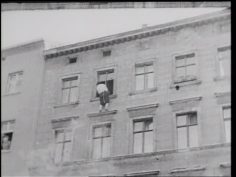 stockvideo's en b-roll-footage met b/w 1961 low angle person on window ledge of building on border of east west berlin / germany / newsreel - ontsnappen