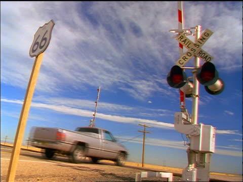 vídeos y material grabado en eventos de stock de canted low angle pickup truck crossing railroad crossing on route 66 / blue sky background / southwest us - route 66