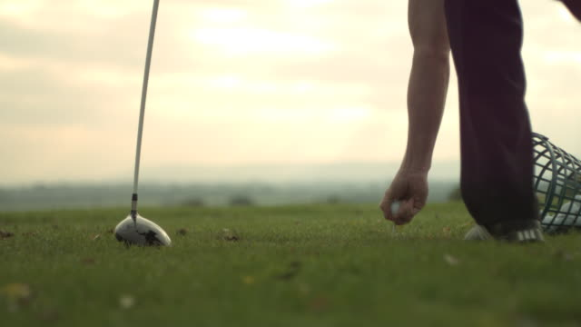 low angle placing tee in grass, dawn background - tee off stock videos & royalty-free footage