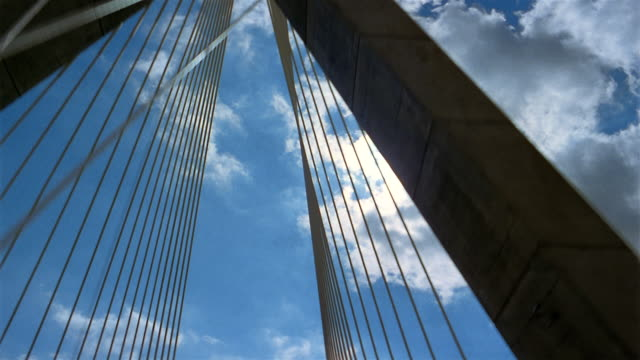 low angle point of view driving across leonard p. zakim bunker hill bridge with clouds in blue sky overhead / boston - ザキム・バンカーヒル橋点の映像素材/bロール
