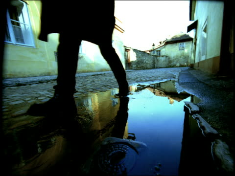 stockvideo's en b-roll-footage met low angle point of view man walking backwards + then forward through puddle on cobblestone street / prague - kassei