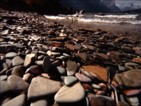 low angle point of view over rocks on beach toward lake lapping at shore / mountains background / glacier natl park, montana - アメリカグレイシャー国立公園点の映像素材/bロール