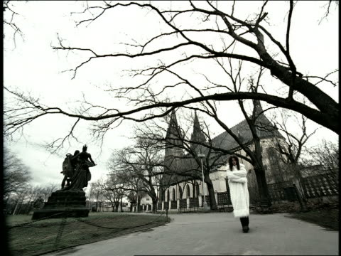 vídeos de stock e filmes b-roll de b/w high contrast low angle point of view past woman in white fur coat walking on sidewalk with church in background / prague - alto contraste