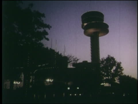 1964 low angle point of view silhouetted tower building at dusk / ny world's fair - 1964年点の映像素材/bロール