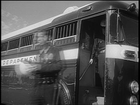 stockvideo's en b-roll-footage met b/w 1965 low angle policemen exiting police bus after watts race riots los angeles / newsreel - 1965