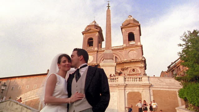 stockvideo's en b-roll-footage met low angle portrait bride + groom exchanging kisses standing in front of trinita dei monti / rome, italy - italian culture