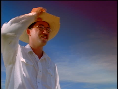 low angle PORTRAIT cowboy with eyeglasses taking off hat + wiping brow / blue skies in background