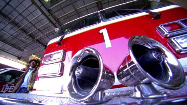 vídeos y material grabado en eventos de stock de low angle ms pan portrait fire truck with black fireman walking up + leaning against it in fire station - un solo hombre de mediana edad