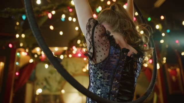 Low angle portrait of aerialist performing on hanging hoop in nightclub / Provo, Utah, United States