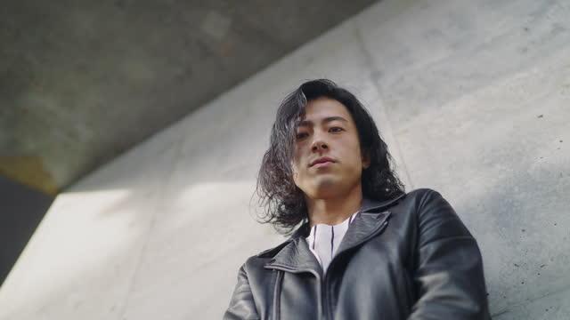 vidéos et rushes de verticale d'angle bas du jeune homme beau frais utilisant la veste en cuir et se penchant contre le mur en béton - vue en contre plongée