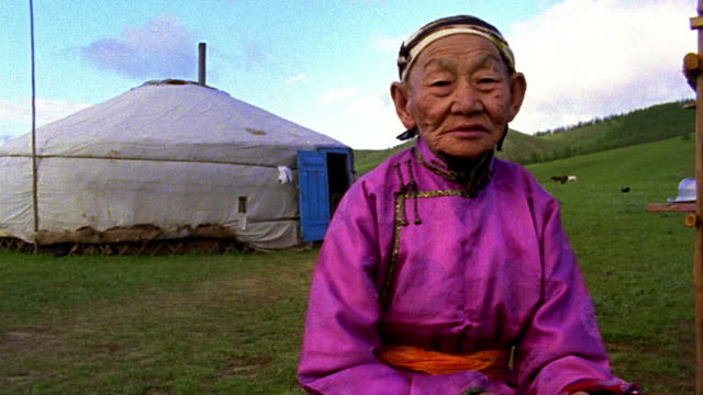 stockvideo's en b-roll-footage met low angle ms portrait senior asian woman wearing traditional clothing sits outdoors with ger in background - mongolië