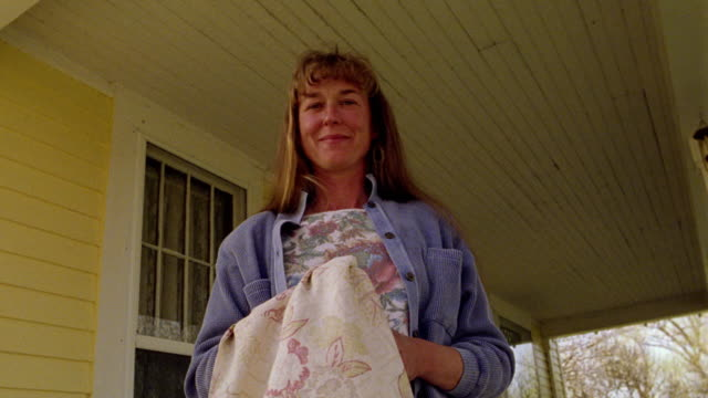 vidéos et rushes de low angle ms portrait woman standing on porch holding table cloth smiling / montana - montana