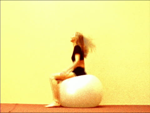 grainy low angle profile young blond woman sitting on large exercise ball bouncing on butt - pallone per fitness video stock e b–roll