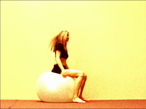 grainy low angle profile young blonde woman sitting on large exercise ball bouncing on butt - pallone per fitness video stock e b–roll