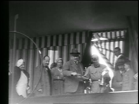 vídeos de stock e filmes b-roll de b/w 1933 low angle race car driver holding trophy surrounded by people after monaco grand prix - 1933