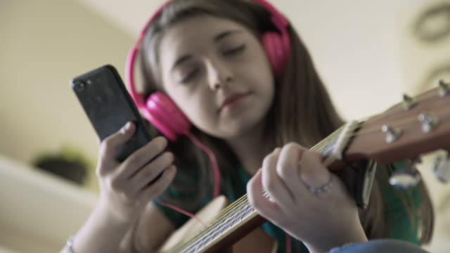 Low angle rack focus of teenage girl using smart phone while playing guitar at home
