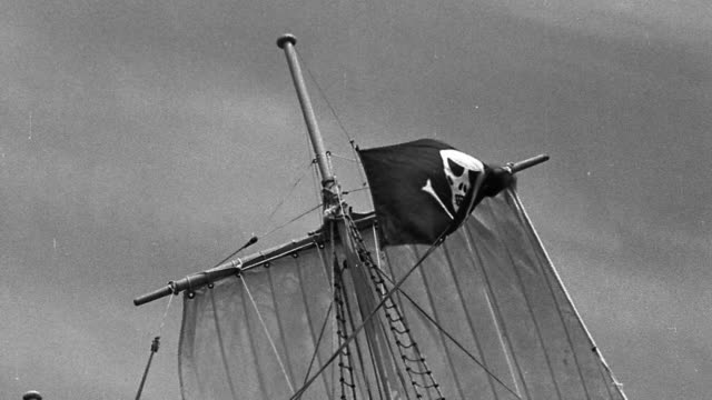 b/w low angle ms raising pirate flag on mast of sailing ship - seeräuber stock-videos und b-roll-filmmaterial