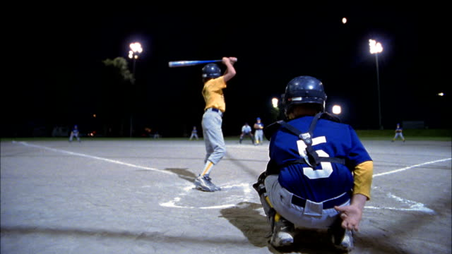 stockvideo's en b-roll-footage met low angle rear point of view little league batter swinging and missing pitch / seattle, washington - baseball uniform