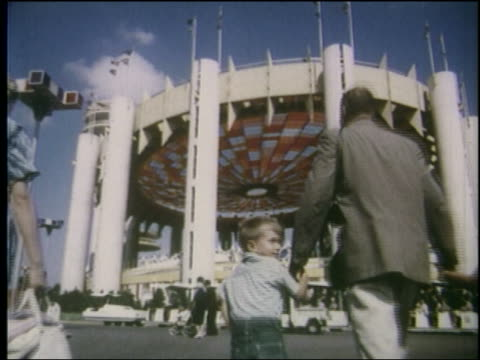1964 low angle rear view family walks toward round pavilion with stained glass ceiling - 1964年点の映像素材/bロール