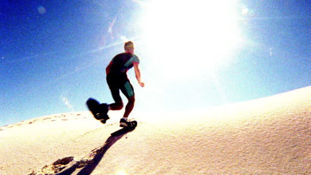 OVEREXPOSED low angle REAR VIEW man running in sand shoes over sand dune / White Sands, New Mexico