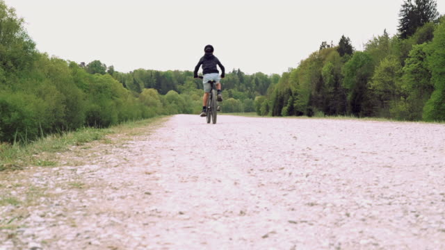 low angle rear view of boy cycling along on a trail - 8 9 years stock videos & royalty-free footage