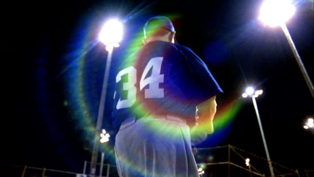 Low angle rear view of Little League pitcher throwing ball at night / Seattle, Washington