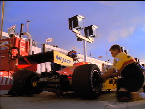 low angle rear view pit crew quickly changing wheels on race car as driver watches / indy racing league - formula one racing stock videos & royalty-free footage