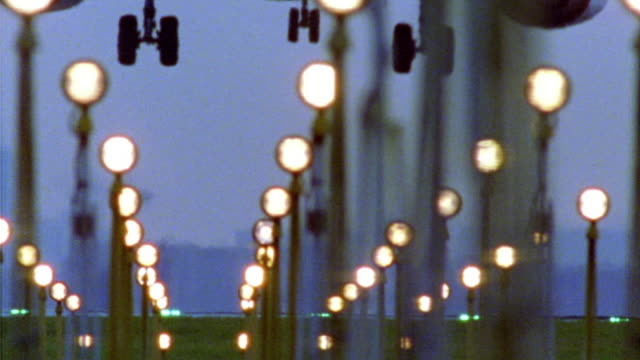 stockvideo's en b-roll-footage met low angle rear view runway lights on with airplane landing at dusk / belgium - landen