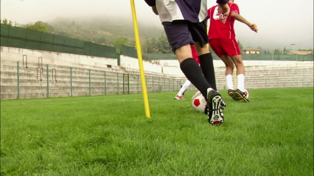 low angle rear view three soccer players dribbling balls around posts - pole stock videos & royalty-free footage
