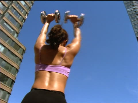 low angle rear view tilt up tilt down woman lifting dumbbells above head on roof of building / buildings in background / nyc - dumbbell stock videos & royalty-free footage
