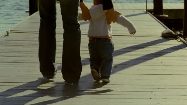 low angle rear view woman helping baby to walk on pier - erste schritte stock-videos und b-roll-filmmaterial