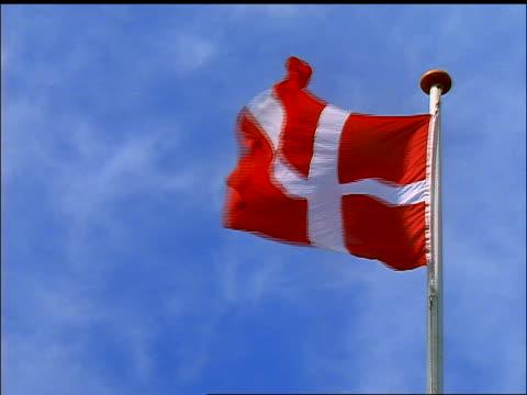 vídeos y material grabado en eventos de stock de low angle red danish flag blowing in wind / blue sky in background / denmark - danish flag